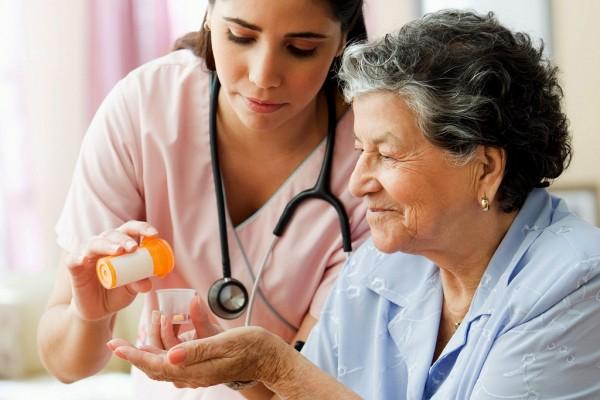 Hispanic nurse helping senior woman with medication