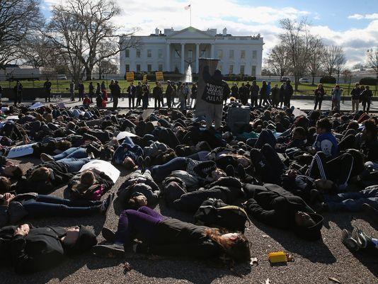 Simulando la muerte de sus compañeros de la preparatoria de Parkland, FL, estudiantes protestan frente a la Casa Blanca por la falta de control en la venta de armas de alto poder. Foto: www.usatoday.com.