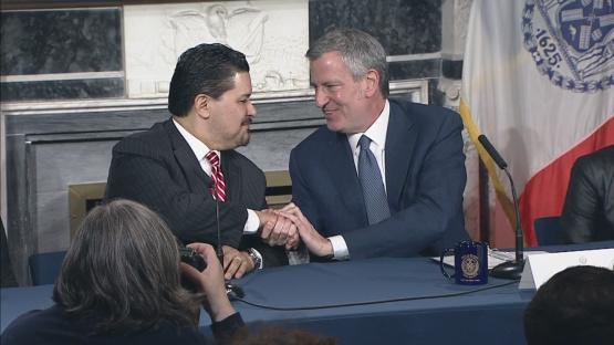 Cerrando el trato de su nueva contratación como canciller escolar, con un apretón de manos Richard A. Carranza mira de frente al alcalde de Nueva York, Bill de Blasio, en el Salón Azul de la alcaldía neoyorquina. Foto: CBS News.