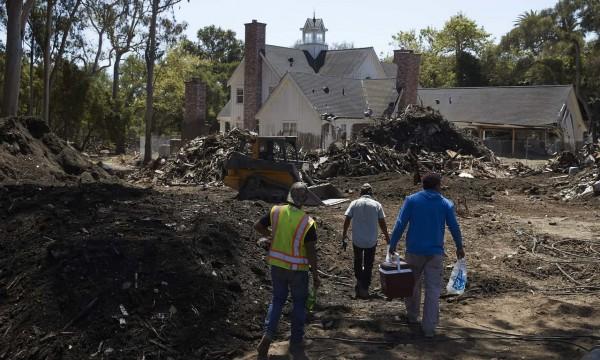 Trabajadores caminan en el barro y los escombros fuera de una casa muy dañada por un alud de lodo en Montecito, California. Foto; The Guardian / AP.