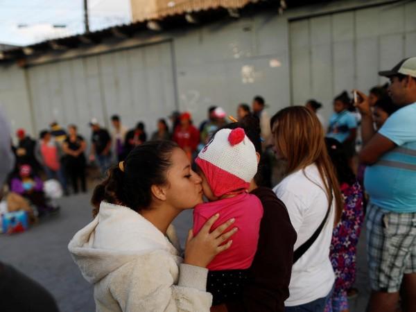 Mujer de una familia migrante besa aun bebé en la línea fronteriza a done llegaron a pedir asilo en la frontera de San Ysidro, California y Tijuana. Foto: WNPR.