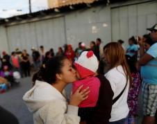 Mujer besa aun bebé de una familia migrante en la línea fronteriza a done llegaron los miembros del la Caravana del Viacrucis Migrante en Tijuana. Foto: WNPR
