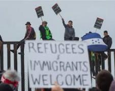 Dan la bienvenida a los migrantes centroamericanos de la Caravana del Viacrucis Migrante en la barda metálica que divide a México de Estados en Playas de Tijuana. Unidos Foto: www.businesinsider.com.