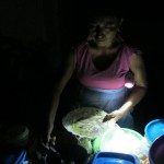 Una mujer en Santa María del Mar prepara comida con la luz de una lampara, tras conflicto de pueblos.