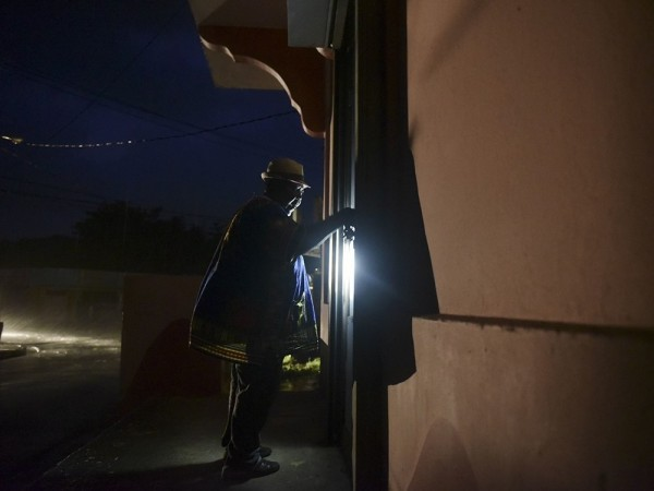 Puertorriqueño ingresa a su casa en la oscuridad de la noche que ha dejado a su paso el Huracán María. Foto: www.nationalpost.com.