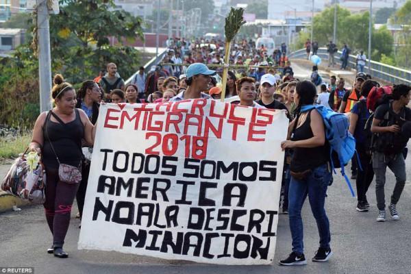 """Unos mil 200 inmigrantes de Centroamérica se dirigieron a pie a Estados Unidos. En la foto, el Domingo de Ramos marchan por el sur de México con un letrero que dice """"Todos somos estadunidenses no a la discriminación"""". Foto: http://www.dailymail.co.uk/."""
