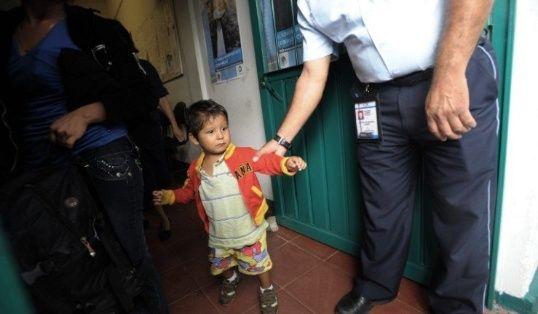 Un oficial de inmigración mexicano sostiene por el brazo a un niño centroamericano mientras su madre es deportada. Foto: AFP.