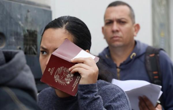 Un inmigrante tapa su rostro con un pasaporte antes de presentarse ante las autoridades de Inmigración en la frontera de Texas. Foto: Prensa Libre.