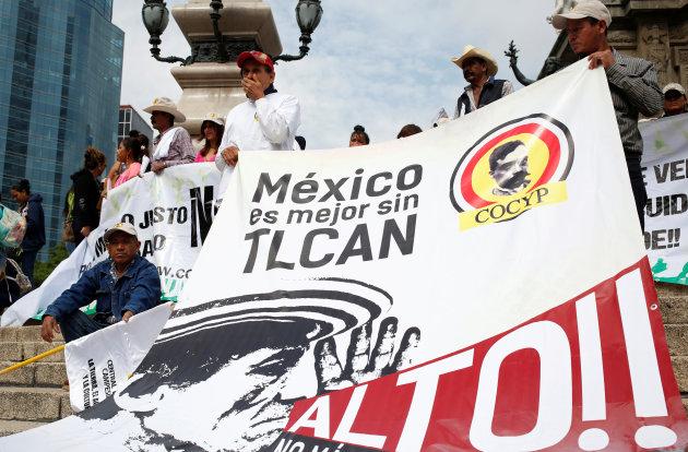 Agricultores de diferentes estados mexicanos, sosteniendo una pancarta, al concluir una marcha contra el Tratado de Libre Comercio de América del Norte en el monumento al ángel de la Independencia en la ciudad de México. Foto: Huffington Post Canada.