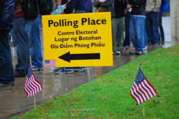 Haciendo la fila para depositar el voto en una casilla electoral. El letrero que lo anuncia está en 4 idiomas.  Foto: iStock.