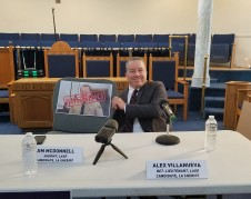 Alex Villanueva, posa con foto de su rival, Jim McDonnall, que no asistió al debate.