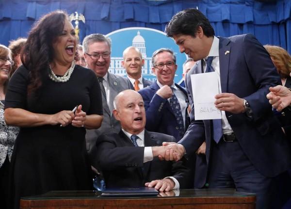 El gobernador de California, Jerry Brown tras firmar la SB 100 estrecha la mano con el autor de la ley, senador demócrata de Los Ángeles, Kevin de León en Sacramento. Foto: www.sacbee.com.