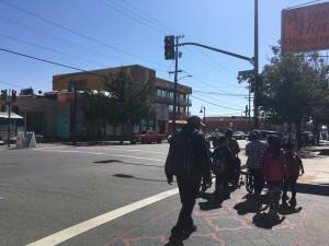 Familias caminan por el barrio de Fruitvale, donde se encuentra la Clínica de la Raza.