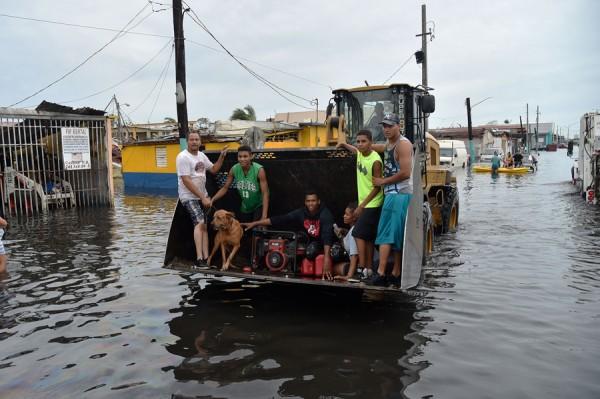 Las personas son transportadas sobre el agua de las inundaciones provocadas por el huracán María, transitan por las calles convertidas en laguna, en Juana Matos, Cataño, Puerto Rico, 21 de septiembre de 2017. Foto: The Atlantic.