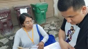 Cynthia Guerra revisa junto con José Flores las direcciones de las casas que visitarán esa tarde.