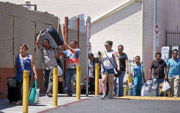 Un grupo que lleva maletas y mercancías se dirige hacia la entrada del cruce de la frontera de México en San Ysidro, California. Foto: Los Angeles Daily News.