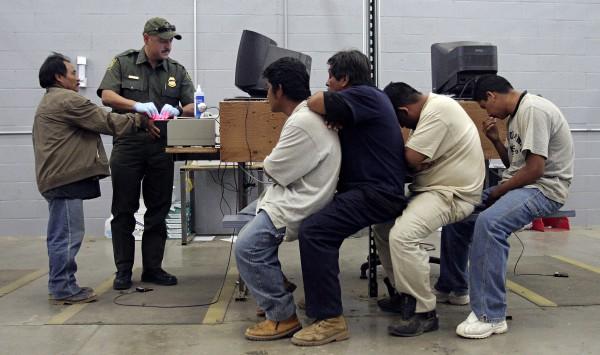 Agente de Inmigración imprime las huellas digitales y las escanea electrónicamente para formar los expedientes de este grupo de migrantes detenidos que esperan su turno en el centro de detención de la Patrulla Fronteriza de Estados Unidos Foto. Reuters / Jeff Topping.