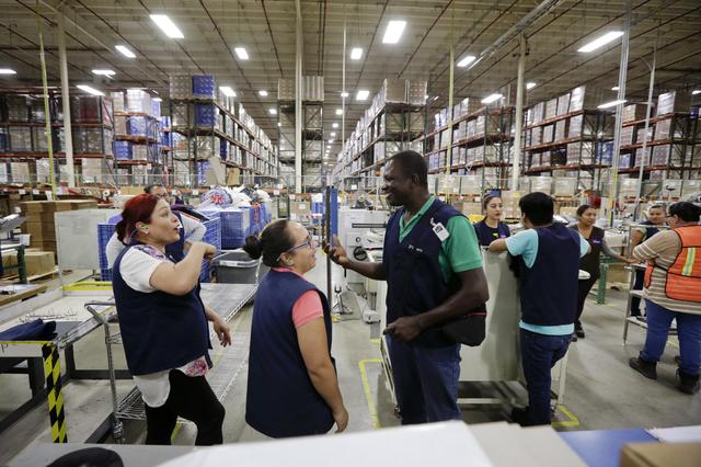 Evens Presendeaux de Haití, habla con compañeros de trabajo en el piso de una fábrica en Tijuana, México. Foto: The Seattle Times.