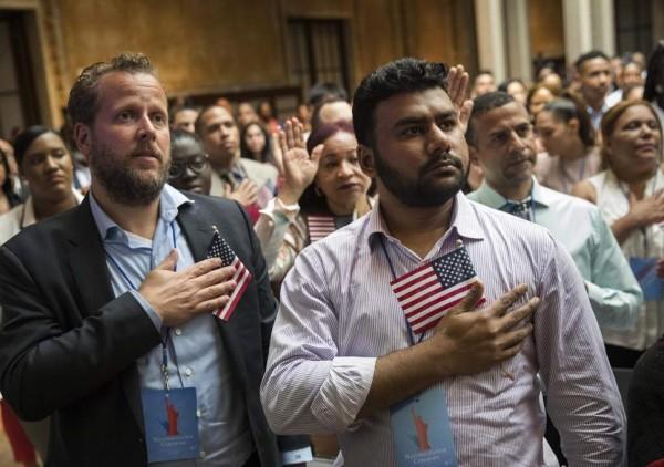 Los nuevos ciudadanos de Estados Unidos recitan el juramento de lealtad durante la ceremonia de naturalización. La regla de carga pública no los afectará retroactivamente. Foto: The Independent.