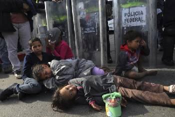 Los niños migrantes descansan en el suelo frente a una fila de policías mexicanos con equipo antidisturbios, después de que intentaron cruzar el cruce fronterizo de Chaparral en Tijuana. Foto: Free Press.