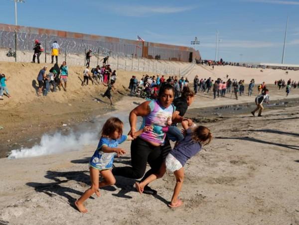 Corriendo con sus hijos para salvarse de las bombas de gas lacrimógeno que les lanzaron los agentes de Inmigración a los migrantes centroamericanos de la caravan este domingo. Foto: Reuters.