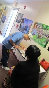 Preso firma a la entrada de las clases de ACTA , lo observa la administradora del programa Vicky Grace.