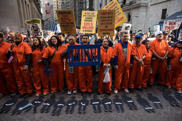 Activistas vestidos de prisioneros se unieron en el distrito financiero de Wall Street en Nueva York, contra el apoyo de las instituciones financieras a las prisiones privadas y los centros de detención de inmigrantes Foto: Drew Angerer / Getty Images.