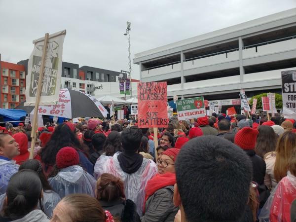 Manifestación de maestros a un lado de oficinas de Asociación de Escuelas charter al fondo, les habla el presidente del sindicato Alex Caputo-Pearl.