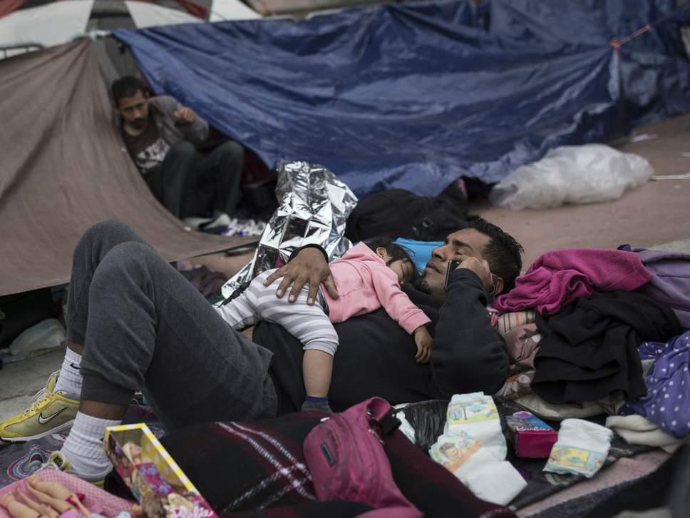 Un padre migrante y un niño descansan donde acampan para esperar el acceso a solicitar asilo en la frontera entre EE. UU. Y México en Tijuana, México (AP Photo / Hans-Maximo Musielik).
