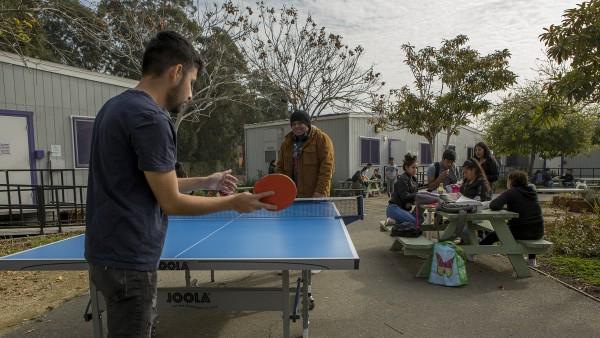 Los estudiantes juegan un juego de ping-pong durante el almuerzo mientras sus compañeros de clase los ven jugar y platican en el patio de la Escuela Secundaria Rudsdale Newcomer, en Oakland el 28 de enero de 2019.