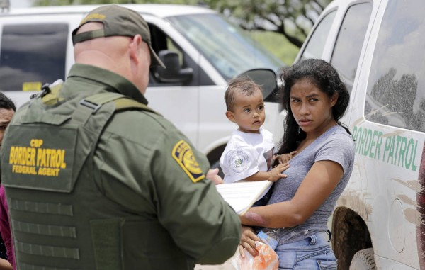 Una madre que migra de Honduras sostiene a su hijo de 1 año mientras se rinde ante un agente de la Patrulla Fronteriza en busca de asilo. Foto: Las Vegas Review-Journal.