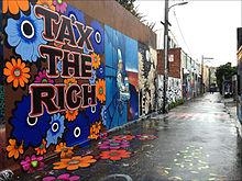 Mural de Megan Wilson, en una de las calles de La Misión, en el área de La Bahía en San Francisco, alusiva a un lema de política y equidad social. Foto: Wikipedia.