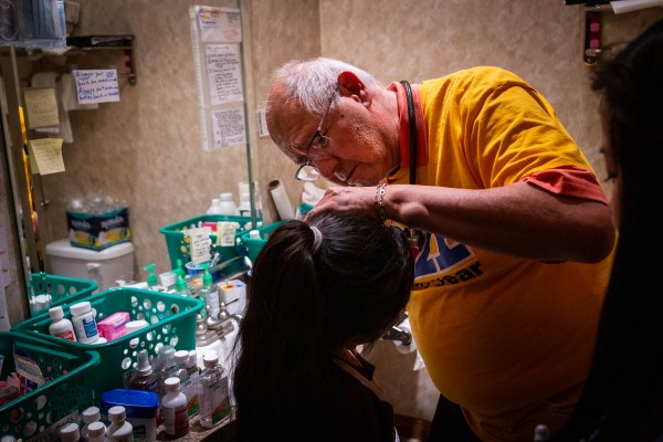 Dr. Carlos Gutiérrez examines a young girl in a makeshift clinic at a shelter in El Paso.Thegirl's mother said she had developed a deep cough while in immigration custody.(Anna Maria Barry-Jester/Kaiser Health News).