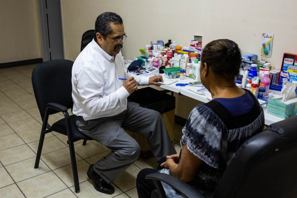 Dr. José Manuel de la Rosa writes a prescription at a makeshift clinic in an old warehouse in El Paso. (Anna Maria Barry-Jester/California Healthline).