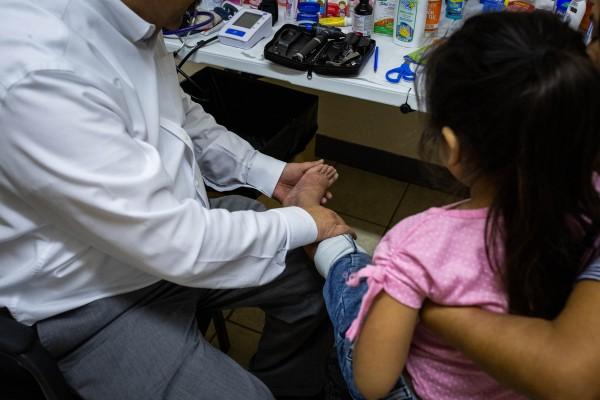 De la Rosa examina una erupción en las piernas de Meliza, de 5 años. Aunque creía que era probable que fuera una reacción alérgica, los moretones aumentaron la preocupación por algo más serio (Anna Maria Barry-Jester / California Healthline).
