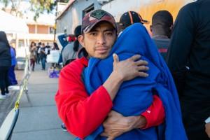 José Manuel Salinas, de Acapulco, México, sostiene al bebé de su amigo mientras espera que lo vea una enfermera. Salinas dice que le tomó cerca de un mes caminar y hacer varias paradas para llegar a la ciudad fronteriza de Tijuana, BC. Él había estado luchando contra un resfriado durante aproximadamente dos semanas, dice.