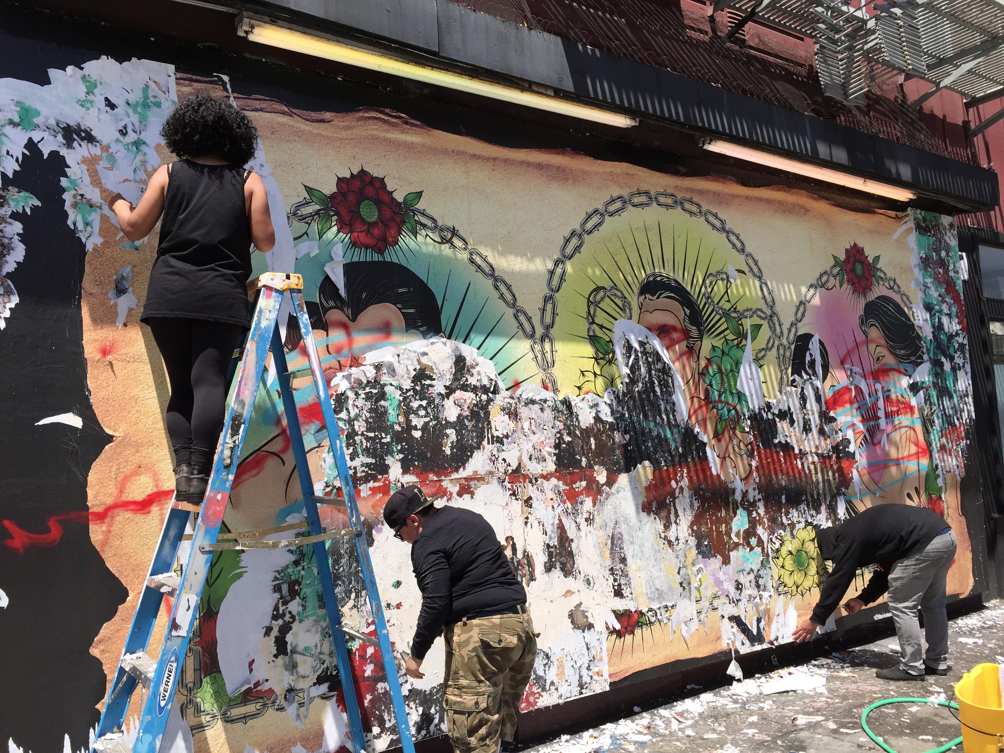 Tres voluntarios que raspan el mural desfigurado de la pared en la Galería de la Raza en la 24ª y Bryant en el Distrito de la Misión de San Francisco (Cy Musiker). Foto: KQED