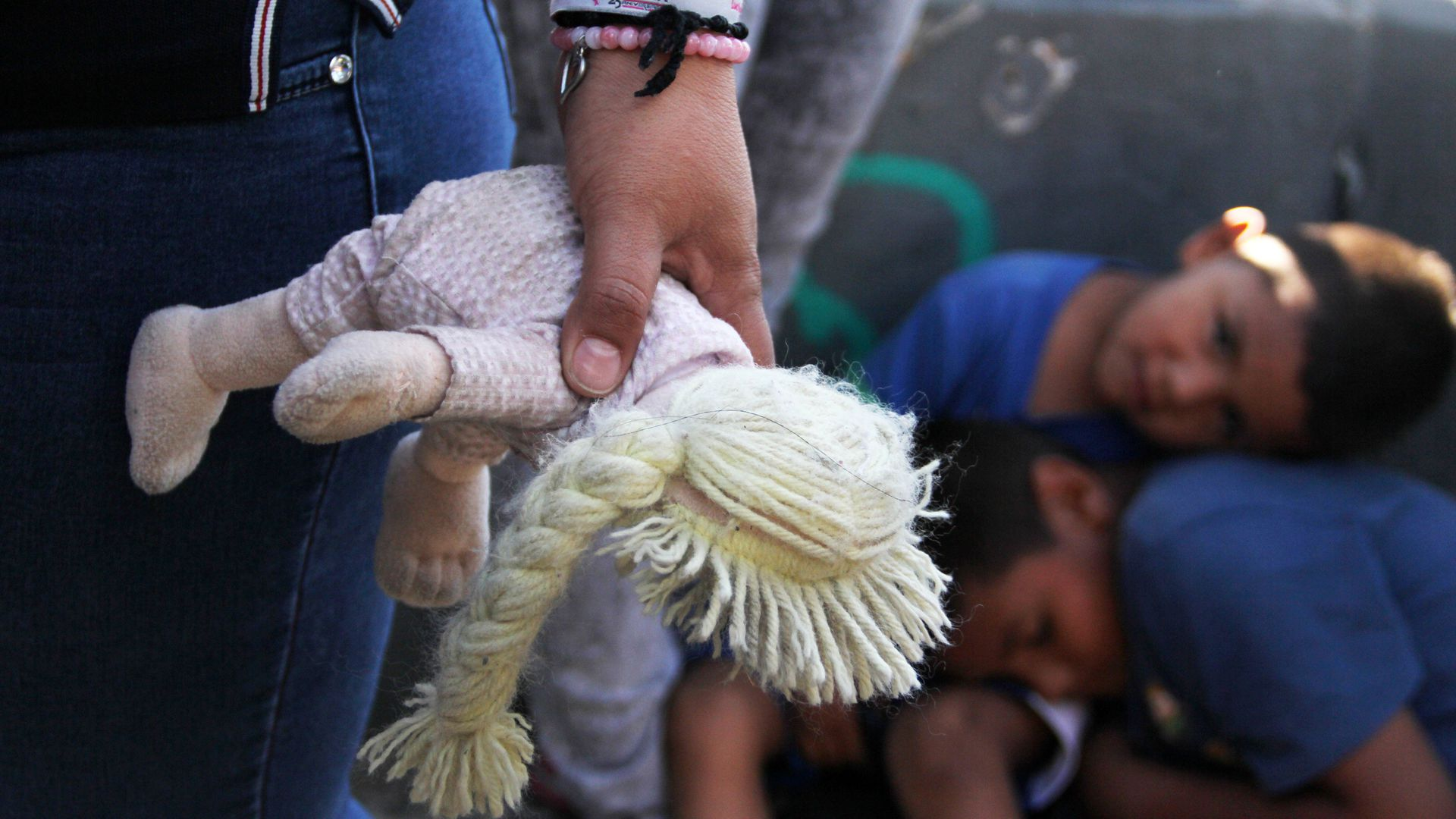 A Mexican woman holds a doll next to children at the Paso Del Norte Port of. Foto: Axios.