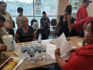María Mesa, recibe instrucciones de Ronald Lira, voluntario de la Cruz Roja. Rubicely su vecina, la acompañan.