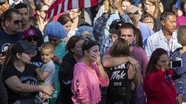 La gente mira con tristeza y horror  la procesión llevando el cuerpo de un sargento del sheriff en el tiroteo masivo del condado de Ventura. Foto: Axios.