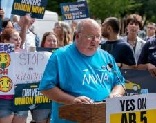 Mike Robinson, de 58 años de Loma Linda, quien ha estado conduciendo Lyft durante cuatro años y dice que aprobar el AB 5 permitirá a los conductores sindicalizarse y aumentar los salarios, habla en un mitin en apoyo del proyecto de ley frente al capitolio de California. Foto: CalMatters.