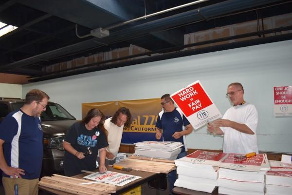 Michael Shimpock, Director de Comunicaciones de la UFCW - Local 770, observa cómo una trabajadora arma la pancarta. Fto: Cortesía del sindicato UFCW.