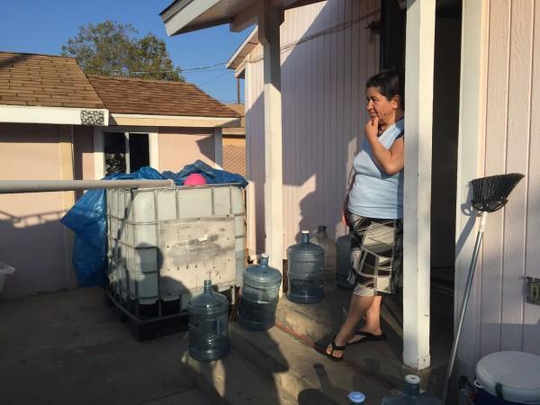 Una organización sin fines de lucro local donó e instaló un tanque de 265 galones en la casa de Socorro Ambriz en East Porterville, California. Cada semana, el hermano de Ambriz llena tres barriles de 55 galones en una estación de agua cercana; él hace dos viajes para que su familia de cuatro se pueda duchar, tirar de los inodoros y lavar los platos. Foto: Joanna Lin / Reveal.