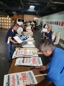 Trabajadores voluntarios laboran a todo vapor construyendo las pancartas.