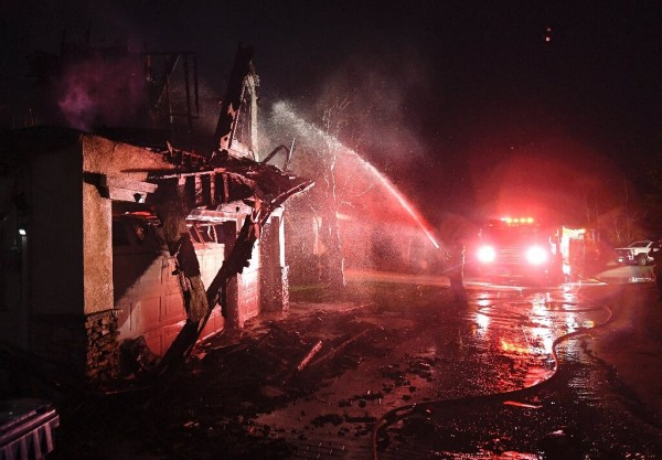 Los bomberos echan agua a presión con sus mangueras en una casa en llamas cerca de Santa Clarita, California. Foto: www. phys.org.