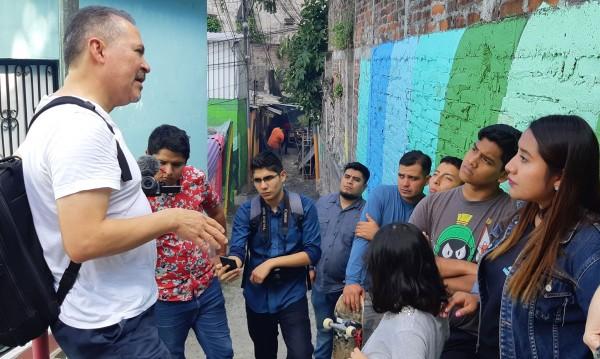 Oscar Chacón, Director ejecutivo y Cofundador de Alianza Américas, de camisete blanca y mochila a la espalda habla con un grupo de migrantes en un barrio popular de el Salvador. Foto: Cortesía de Alianza Américas.