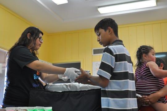 Joven recibe alimentos en el Centro de Recreación de Central Park en Salinas, California, uno de los múltiples lugares que distribuye comidas gratis para niños desamparados menores de 18 años durante el verano. Foto: www.thecalifornian.com / Eduardo Cuevas.