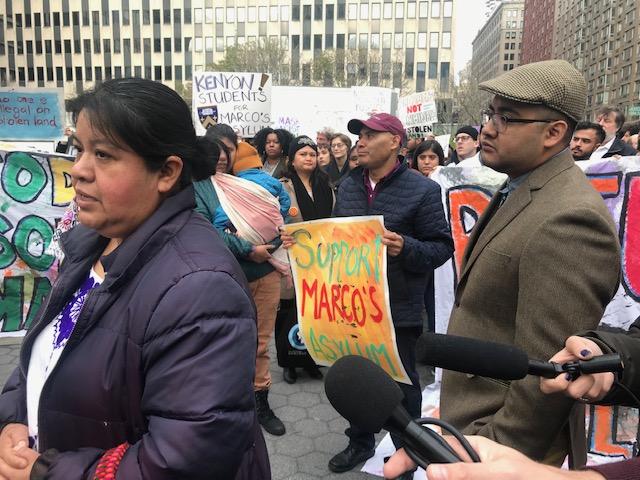 En la conferencia de prensa, antes de entrar a la corte Natalia Méndez, madre de Marco Saavedra habla a la prensa sobre el caso legal de su hijo y las expectativas de obtener asilo. Y en la parte de atrás, a la derecha Marco, y a la izquierda su padre, Antonio Saavedra sostiene un cartel de apoyo a su hijo.
