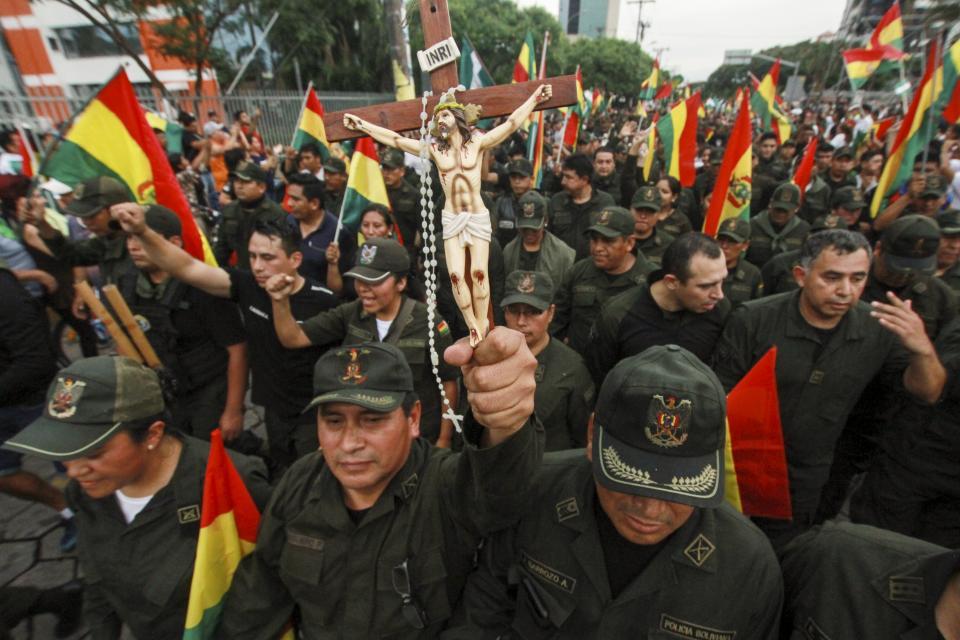 Policías, con crucifijo en mano, salen a reprimir en Bolivia. Foto: Internet / www.ollantayitzamna.com.