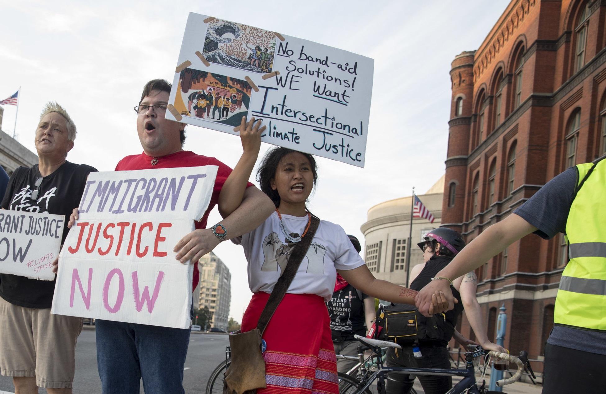 """Los manifestantes marcharon por K St. NW, con carteles que decían """"Justicia climática"""", """"Advertencia"""" y """"No se puede beber petróleo"""", además de pedir justicia para los inmigrantes. Foto: https://wamu.org."""